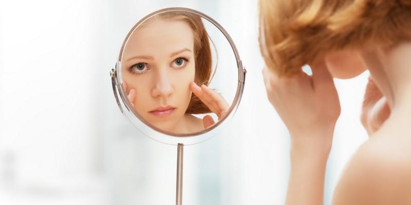 Frau betrachtet ihr Gesicht im Spiegel