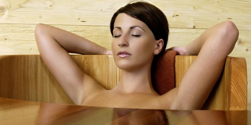 Frau badet in einer Holzbadewanne